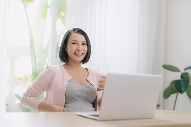 Zwangere vrouw die op laptop thuis werkt