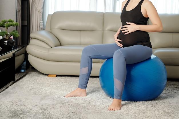Zwangere vrouw die op yogabal uitoefent