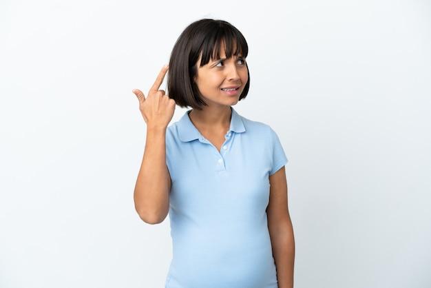 Zwangere vrouw die over geïsoleerde witte achtergrond het gebaar van waanzin maakt en vinger op het hoofd zet