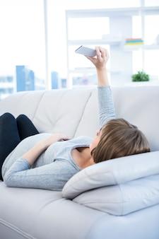Zwangere vrouw die selfie thuis smartphone gebruiken klikken