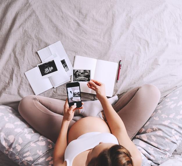 Zwangere vrouw die smartphone in handen houdt met leeg wit display