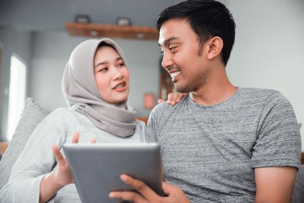 Zwangere vrouw die tabletpc met echtgenoot met behulp van