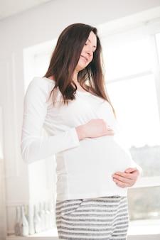 Zwangere vrouw die thuis en buik loopt te houden