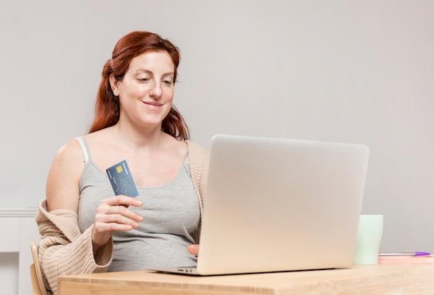Zwangere vrouw die thuis online het winkelen doet