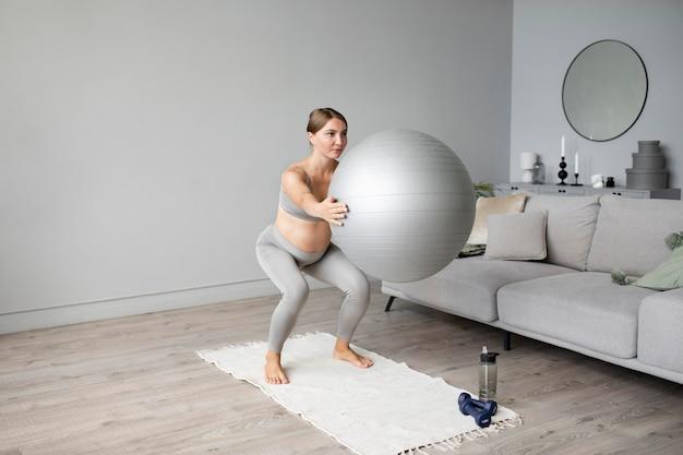 Zwangere vrouw die thuis traint