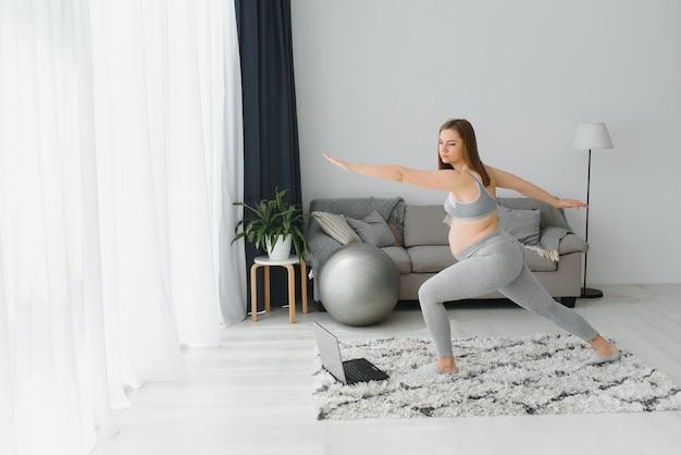 Zwangere vrouw die thuis yoga beoefent met laptop. aanstaande moeder doet prenatale videotraining binnenshuis. vrouwelijke oefening, mediteer tijdens de zwangerschap. online fitnessles op digitale apparaten.