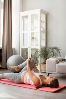 Zwangere vrouw die thuis yoga doet