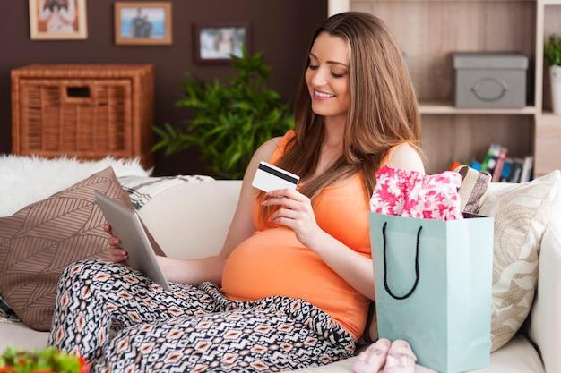 Zwangere vrouw die van online winkelen door digitale tablet geniet