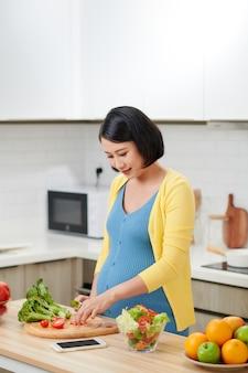 Zwangere vrouw die verse groene salade op keuken mengen.