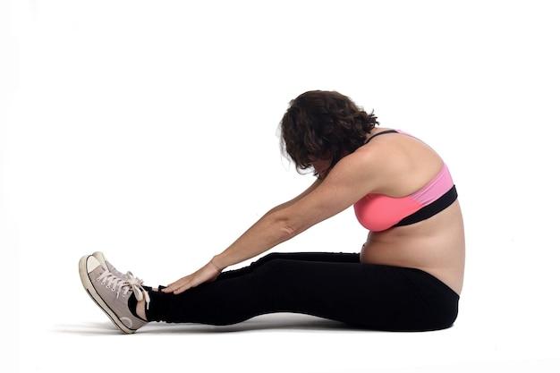 Zwangere vrouw die vloeroefeningen op witte achtergrond doet