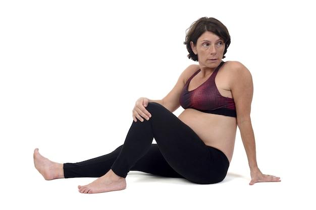 Zwangere vrouw die vloeroefeningen op witte pagina doet, vakrasana
