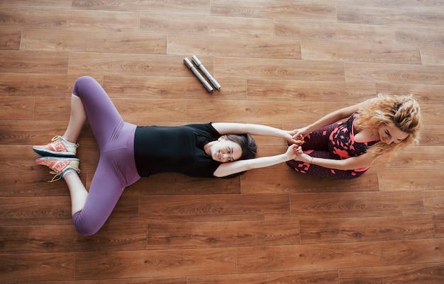 Zwangere vrouw die yoga met persoonlijke trainer doet.