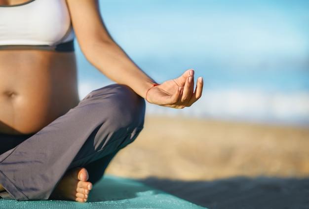 Zwangere vrouw die yoga op het strand doet. zacht licht. mooi meisje met een zwembroek. zee. ze ontspant yoga.