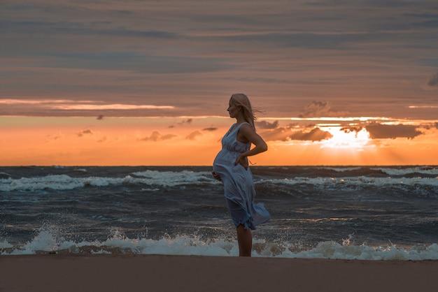 Zwangere vrouw die zich op zee strand bevindt