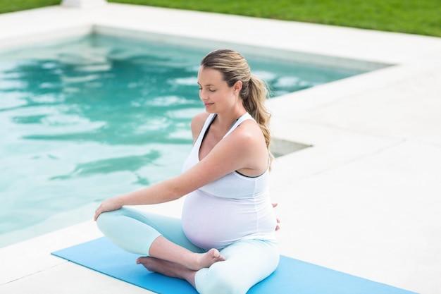 Zwangere vrouw die zich uitstrekt over mat naast het zwembad