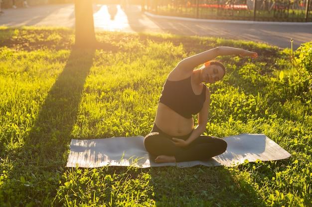 Zwangere vrouw doet fitness oefening op het gras in de zomerdag. gezonde levensstijl.