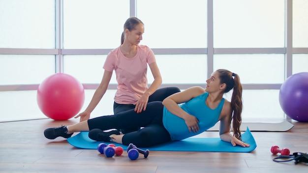 Zwangere vrouw doet oefeningen voor zwangere vrouwen met een personal trainer in een fitnessles. moederschap en sport, zorgen voor je lichaam en gezondheid.