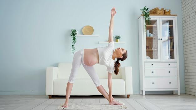 Zwangere vrouw doet utthita trikonasana bij de bank thuis