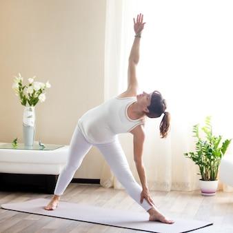 Zwangere vrouw doet utthita trikonasana yoga thuis
