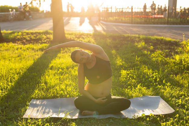 Zwangere vrouw doet yoga in de natuur buitenshuis. gezonde levensstijl, baby en vruchtbaar concept verwachten.