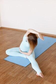 Zwangere vrouw doet yoga op een lichte achtergrond