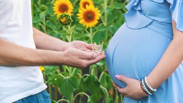 Zwangere vrouw en een man op een zonnebloemgebied