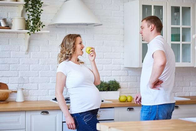 Zwangere vrouw en haar echtgenoot in de keuken thuis met fruit. het gezin wacht op de geboorte van een kind.