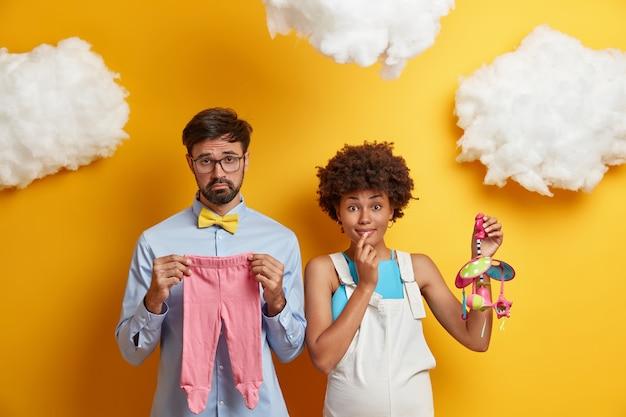 Zwangere vrouw en haar man bereiden zich voor op de geboorte van een kind, kopen kleding en speelgoed voor pasgeborenen, volgen cursussen voor toekomstige ouders, staan tegen geel. ouderschap en zwangerschap concept
