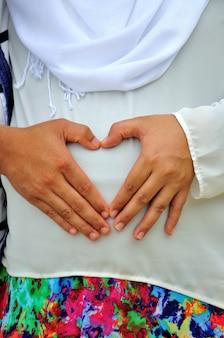 Zwangere vrouw en haar man houden haar handen in de vorm van een hart op haar babybuil.