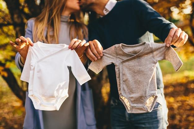 Zwangere vrouw en haar man houden kleding voor pasgeboren baby's in hun hand en kussen elkaar