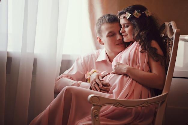 Zwangere vrouw en haar man poseren in een klassiek interieur