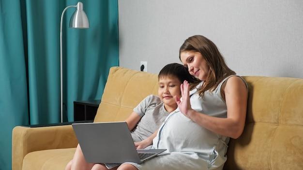 Zwangere vrouw en jongen praten via videogesprek op laptop terwijl ze op de bank zitten
