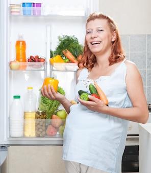 Zwangere vrouw en koelkast met natuurvoedingsgroenten en fruit