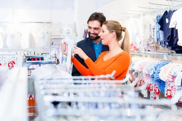 Zwangere vrouw en man het kopen babykleren in opslag