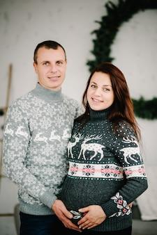 Zwangere vrouw en man in zachte truien in huis gelukkig nieuwjaar en vrolijk kerstfeest