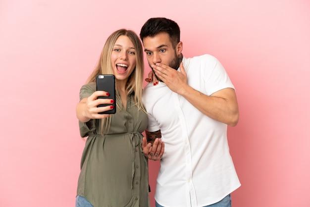 Zwangere vrouw en man over geïsoleerde roze achtergrond maken een selfie met de mobiel