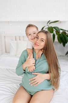 Zwangere vrouw en zoontje raken een dikke buik thuis op het bed, het concept van zwangerschap en wachten op de geboorte van een baby en een tweede kind in het gezin