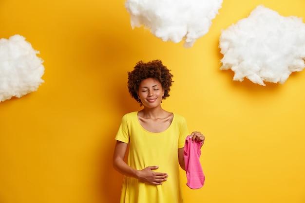 Zwangere vrouw geeft om toekomstig kind raakt buik, staat met gesloten ogen en charmante glimlach, houdt baby singlet vast, bereidt zich voor om moeder te worden, draagt gele jurk voor moeders. pasgeboren verwacht