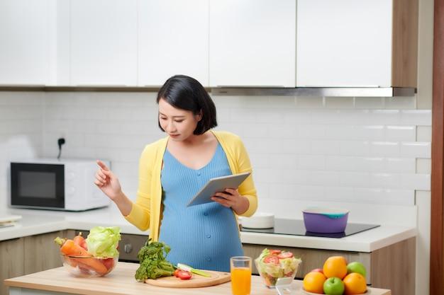 Zwangere vrouw gezonde maaltijd bereiden en veganistische recepten zoeken via draagbare computer binnenshuis.