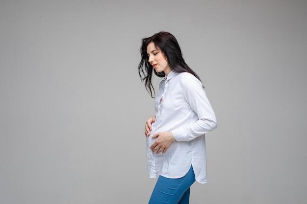 Zwangere vrouw heeft hoofdpijn in de studio