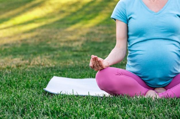 Zwangere vrouw het beoefenen van yoga in de natuur, meditatie en ontspanning buiten