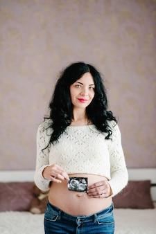 Zwangere vrouw houdt foto of afbeelding op de buik of echografie op de buik