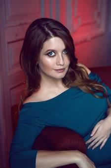 Zwangere vrouw in blauwe jurk liggend op rode sofa in studio