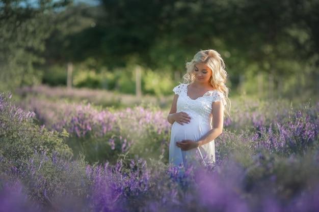 Zwangere vrouw in de natuur. mooie vrouw toekomstige moeder in witte lange jurk op straat