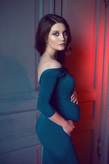 Zwangere vrouw in een lange blauwe jurk die tegen de muur in de studio staat