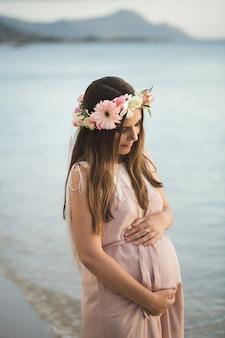 Zwangere vrouw in een mooie jurk op de oceaan.