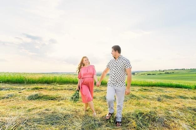 Zwangere vrouw in een roze jurk heeft een boeket bloemen. aanstaande ouders houden elkaars hand vast en lopen in de wei.
