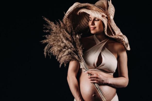Zwangere vrouw in een strohoed met beige kleding met een boeket in haar handen in de studio op een zwarte achtergrond.