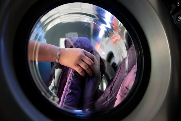 Zwangere vrouw in een wasserij. kleding in de wasmachine doen. uitzicht vanuit het glas van de wasmachine.