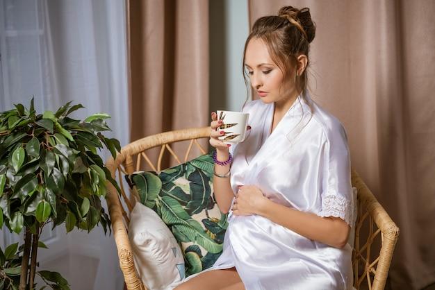 Zwangere vrouw in een witte jas, zittend in een stoel met een mok in haar hand
